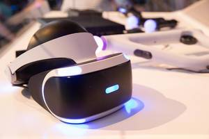 Sony Playstation VR goggles on a white desk with a controller in the background