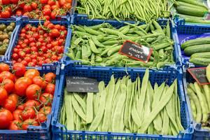 Sortierte Gemüseauslage mit Tomaten, Bohnen, Erbsen und Gurken in blauen Kunststoffboxen