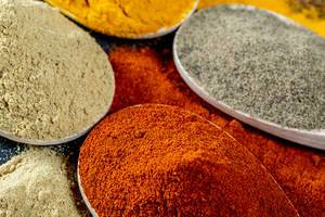 Sortiment an farbenfrohen indischen Gewürzen in Holzgefäßen und auf Tisch