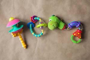 Sortiment an Kinderspielzeug aus Kunststoff für neugeborene Babys auf braunem Papier