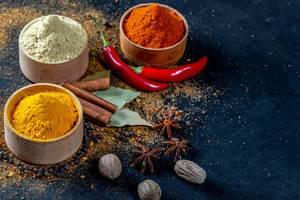 Sortiment aus gemahlenen Gewürzen, ganzen Chilis, Zimtstangen, Muskatnuss und Sternanis
