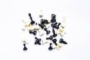 Sortiment aus schwarzen und weißen Schachfiguren verteilt auf weißem Hintergrund