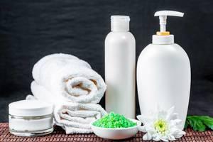 Spa-Utensilien für Hautpflege wie Creme, Seife und Badesalz mit Badetuch vor dunklem Hintergrund