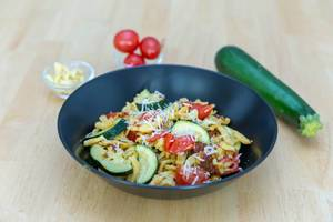 Spaetzle with dried tomatoes and zucchini with ingredients in the background