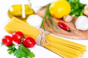 Spaghetti mit Gemüse und Gewürzen, Olivenöl und Chili vor Holzbrett