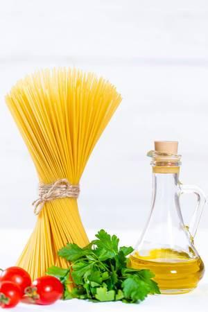 Spaghetti mit kleinen Tomaten, Karaffe mit Olivenöl und Bund Pertersilie