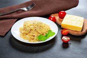 Spaghetti with cheese and sesame seeds on a black background with tomatoes (Flip 2019)