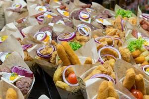 Spanische Tapas in Barcelona: Burritos mit der Paprikawurst Chorizo, Calamari, Seehecht-Fischmischung und frittiertem Hähnchen