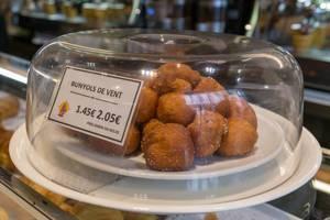"""Spanisches Krapfengebäck """"Bunyols de vent"""" auf weißem Teller unter Tortenhaube in einem Café in Barcelona"""