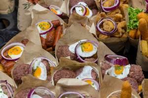 Spanish food stand sells Burritos filled with Chorizo sausages, meatballs, chips, eggs & calamares-merluza fish mix at Mercat de la Boqueria, Barcelona
