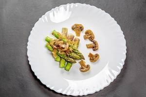 Spargel mit Pilzsauce auf einem weißen Teller auf einem schwarzen Hintergrund Top-view