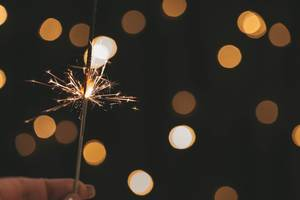 Sparkler in hand on golden bokeh background
