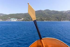 Spartanischer Speer und Schild auf dem Schiff und das Kloster Agios Panteleimon im Hintergrund