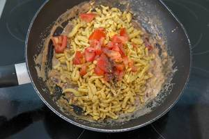 Spätzle noodles with cream sauce and tomatoes being prepared in a wok pan