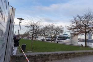 Spaziergängerin fotografiert den Rhein bei hohem Pegelstand