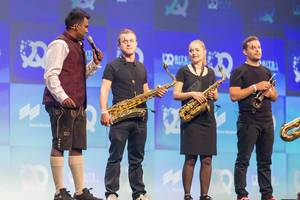 Speaker and Bits & Pretzels Host Dan Ram with Oktoberfest-look in lederhosen, next to trumpeters on stage