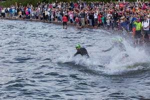 Spectators on the coast of Lake Vesijärvi cheering for Ironman athletes during the swimming competition