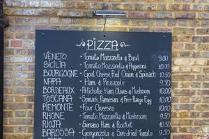 Speisetafel mit vielen verschiedenen Pizzas