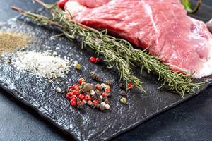 Spices and raw meat steak on black background