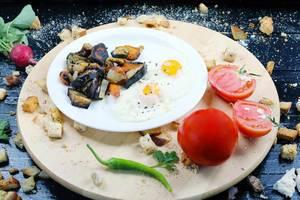 Spiegelei, gegrilltes Gemüse und Tomaten auf einem Holzbrett serviert