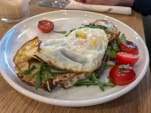 Spiegelei-Omelett auf knusprigem Toast mit Tomaten und Ruccola auf weißem Teller im Nahaufnahme