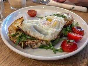 Spiegelei- Omelett auf rustikalem Brot mit Rucola und Tomaten auf weißem Teller in Nahaufnahme