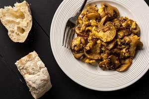 Spiegeleier und Pilze und Brot auf dem Tisch
