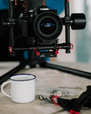 Spiegelreflexkamera eingespannt in Schwebestativ über Tisch mit Kaffeetasse und Zubehör