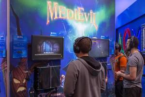 Spielemesse-Besucher mit Kopfhörer, spielen MedieEvil auf der PS4