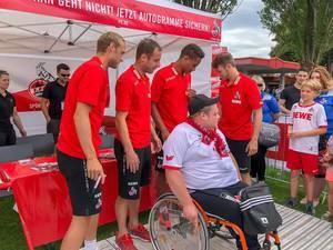 Spieler des 1. FC Köln posieren für Fotos mit einem Fan im Rollstuhl