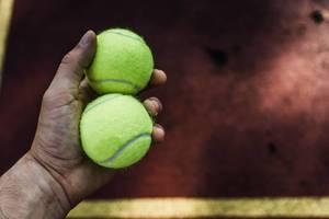 Spieler hält zwei Tennisbälle in der Hand vor dem Aufschlag