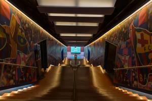 Spielertunnel des FC Barcelona mit aufgemalten Vereinsflaggen an den Wänden und beleuchtetem Treppengang zum Stadion Camp Nou in Spanien