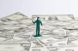 Spielfigur Arbeiter aus grünem Kunststoff steht auf verteilen US-Dollar Banknoten