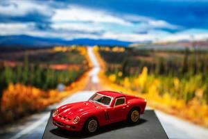 Spielzeug-Ferrariauto auf einer Plattform mit Landschaft im Hintergrund