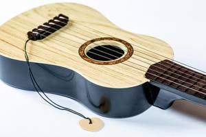 Spielzeug-Gitarre mit Gitarrenplättchen für das Spielen auf den Saiten isoliert vor weiß