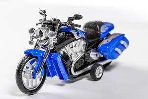 Spielzeug-Motorrad in blau und schwarz vor einem weißen Hintergrund