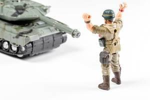 Spielzeug Soldat hält seine Hände hoch vor einem Panzer Konzept Kampf gegen den Verlierer