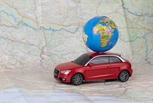 Spielzeugauto mit kleinem Globus auf dem Dach auf einer Landkarte