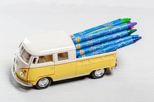 Spielzeugauto mit Wachsmalstiften im Kofferraum auf einem Holztisch