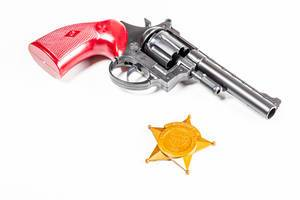Spielzeugpistole und goldene Polizeimarke aus Plastik vor einem weißen Hintergrund