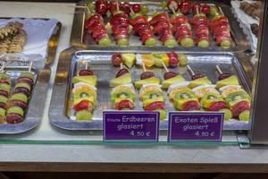 Spieße mit glasierten Früchten wie Erdbeeren, Trauben und tropischen Früchten wie Kiwis und Orangen