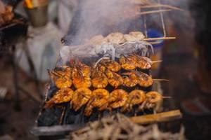 Spieße mit Meeresfrüchten - Garnelen und Tintenfisch schmoren auf dem Grill eines Marktes auf den Phillippinen