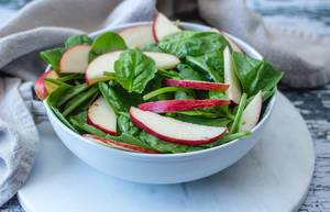 Spinach and Apple Salad in a White Bowl