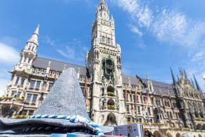 Spitzer, grauer, bayrischer Trachtenhut mit dem Neuen Rathaus am Marienplatz im Hintergrund und wehenden LGBTQ-Regenbogenflaggen für den CSD