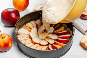 Sponge dough is poured into a baking sheet with apples. Apple pie recipe concept