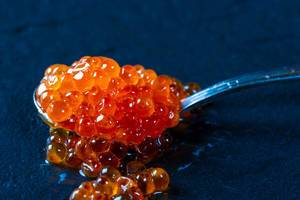 Spoon of red caviar on black background