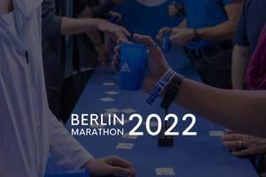 """Sportler am Adidas-Stand mit Getränkebechern und dem Bildtitel """"Berlin Marathon 2022"""""""
