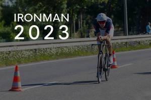 """Sportler beim Radrennen während des Triathlons, neben dem Bildtitel """"Ironman 2023"""""""
