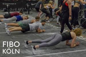 Sportler nehmen an der Plank Challenge teil und machen gemeinsam Fitness, neben dem Bildtitel Fibo Köln