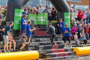 Sports athlete at the finish line for the swimming competition at the Ironman 70.3. at the coast of Lahti, Finland, with a cheering crowd